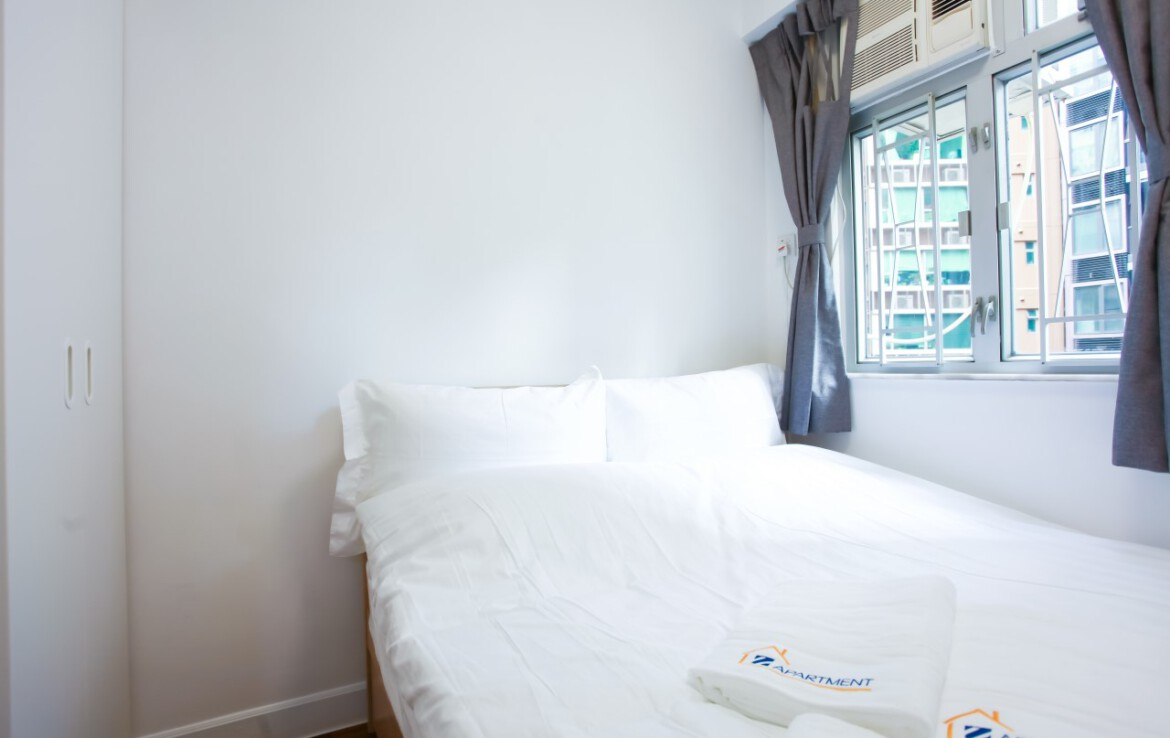 Queen size bed with white wardrobe in Tin Hau 2 BR Apartment