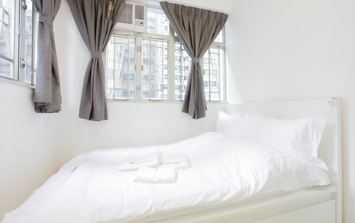 Queen size bed facing window in Fortress Hill Apartment