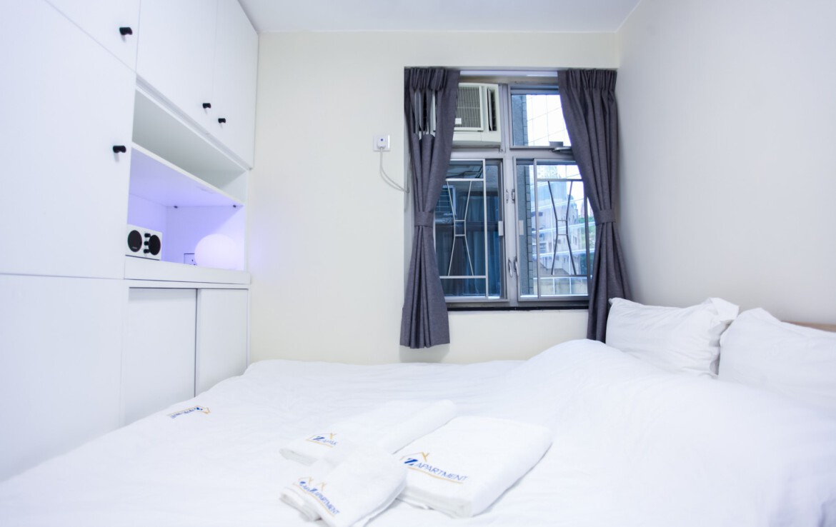 Queen size bed facing window in Fortress Hill 2 bedrooms Apartment