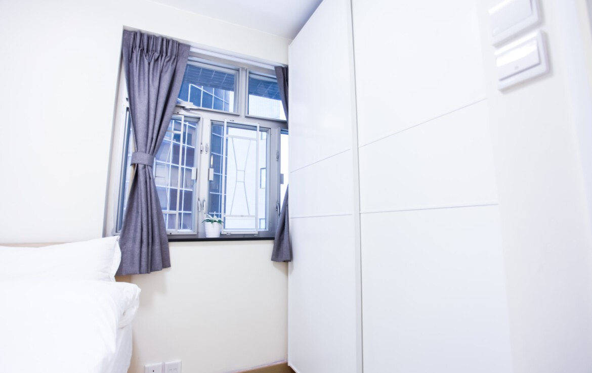 Queen size bed with white wardrobe combination in Fortress Hill 2 BR apartment